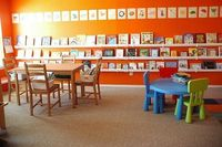 recycled gutters into the book wall...i love this room with its orange book walls!