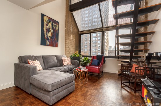 Real Estate photographer work, midtown apartment, view of the living room and the large window, new york city