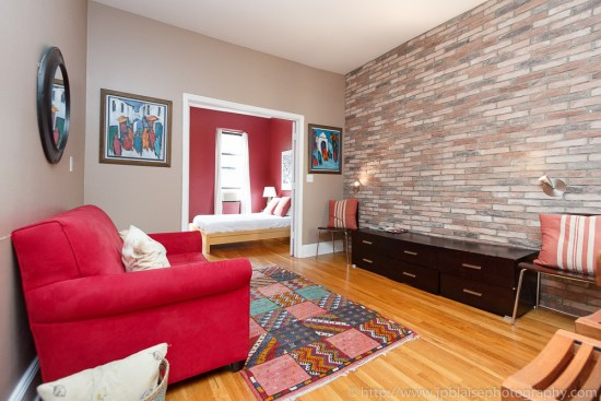 Living room professionally shot with exposed brick wall and red sofa in the upper west side of New York City