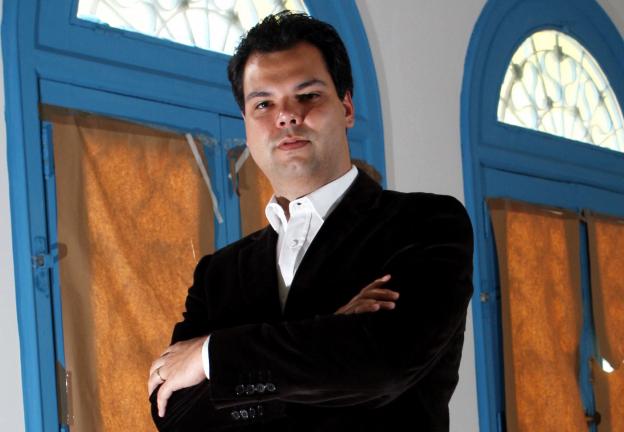 De traje social, Bruno Cova, sem barba, com rosto rechonchudo e cabelo preto, cruza os braços em foto posada em 2010