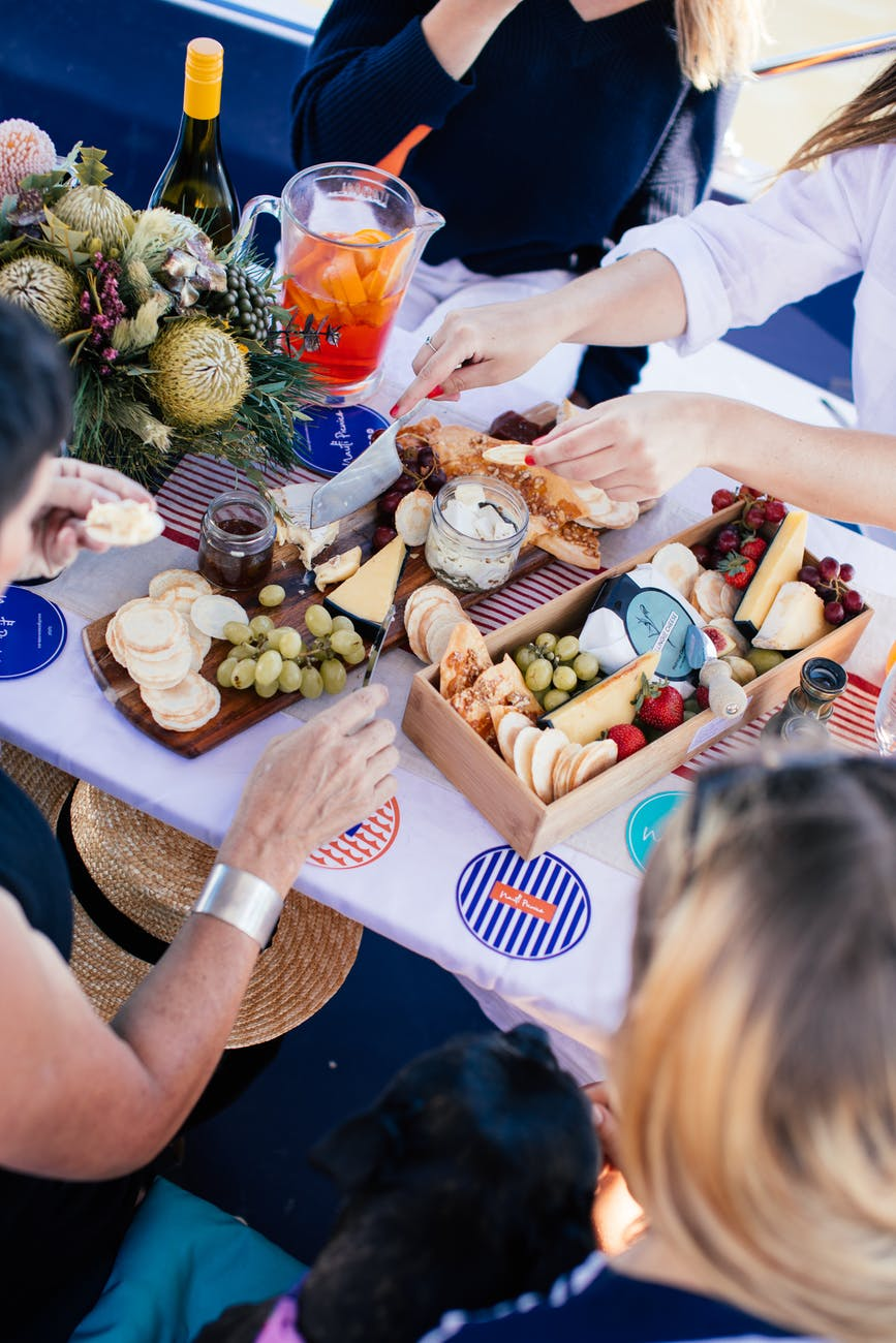 crop people having picnic with drinks and food