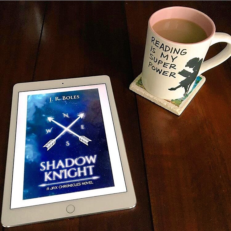 "Alt Text: Image of kindle cover of SHADOW KNIGHT (compass with arrows over blue map with coffee cup showing a woman reading captioned, ""Reading is my super power."""