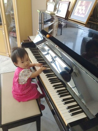 Little E playing the piano by herself