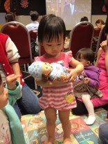 Little E carrying a baby doll.