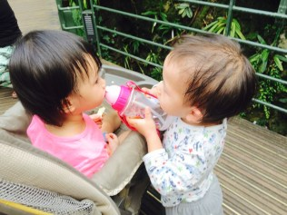 Asher offering a drink to Little E.