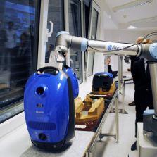 RIF - Labor Dortmund: D er Roboter nimmt den Staubsauger mit einem passiven Greifer vom Werkstückträger und stellt ihn auf dem Arbeitstisch ab.