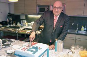 Mit der Erfahrung aus 20 Dienstjahren: Roland W. Waniek schneidet souverän die Torte an. Foto: IKT