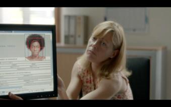 The woman processing Seyna's ID showing her that her her hair doesn't fit in the frame.  From Unifranc.org