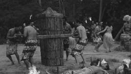 Kimo's tree-trunk coffin is brought to put him in.