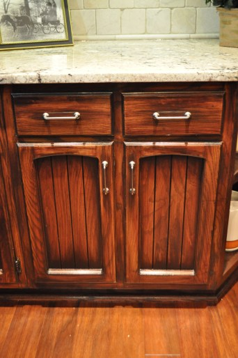 AFTER--A four-step process of refinishing gave the cabinets a richer, antiqued look, contrasting beautifully with the granite counters, and complementing the new Acacia wood floor(9).