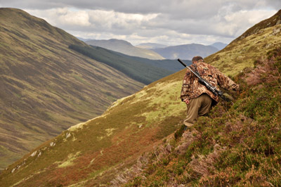 man hiking downhill with a rifle on his back