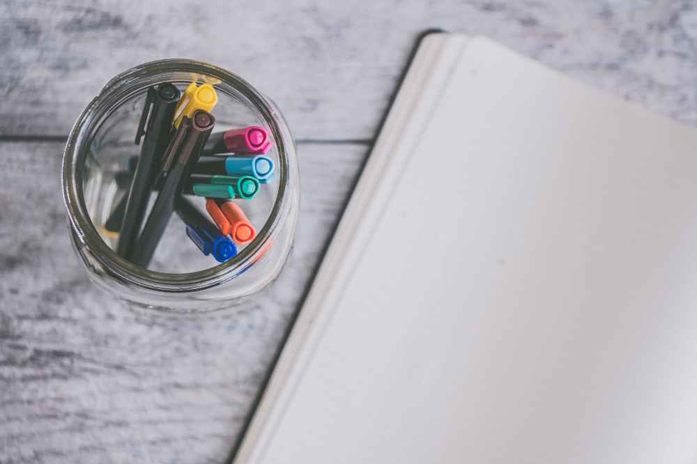 clear glass jar filled of coloring pens beside of white sketch pad