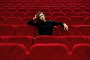 A woman sits in a theatre