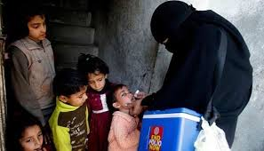 Lady Health workers droping Polio vaccine in kid mouth.