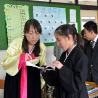 Going old-school: An ethnic Korean teacher in traditional 'chima chogori' dress teaches junior high school students at a Korean school in Yokohama on Feb. 21. | AFP-JIJI
