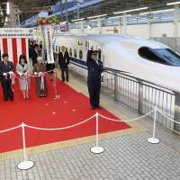 The Nozomi No. 200 superexpress, Wednesday's first bullet train departure from Shin-Osaka Station, is sent off with a ribbon-cutting ceremony. | KYODO