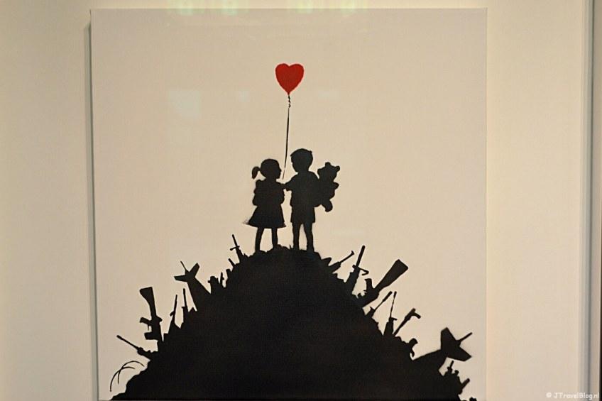 'Kids on Guns' (2003), een silhouet van kinderen op een berg van geweren van Banksy.