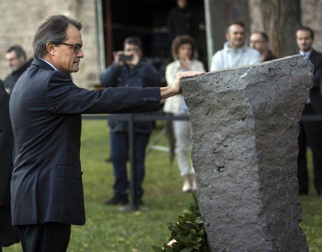 Mas toca el monolito que se encuentra en el luhgar donde fusilaron a Lluís Companys. Una fotografía y un gesto de indudable valor para la causa secesionista. La foto es de elpais.com.