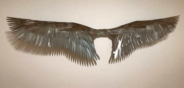 """Aerialist,"" 10' wide wings made of knife blades, depicts risks of flight.."
