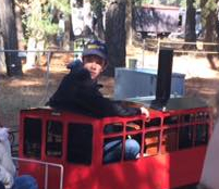 My son driving a model train.