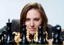 Judit Polgar mriando a la cámara con un tablero de ajedrez en frente