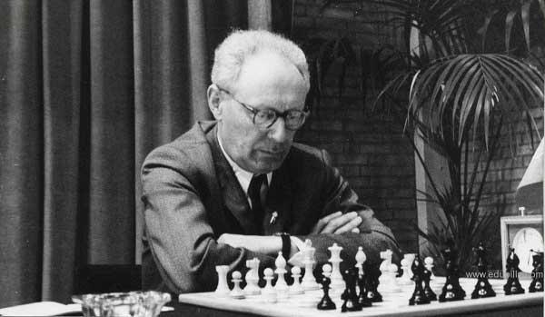 Mijaíl Botvínnik pensando jugando al ajedrez con reloj en un lindo lugar