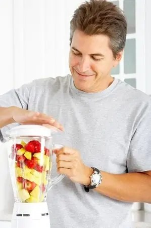 Happy man juicing his natural testosterone booster with a regular blender