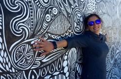 Jules posing next to a graffito in Bondi beach