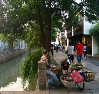 A street vendor rests on the margins of the canal, at Suzhou