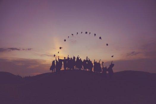 graduates in a sunset