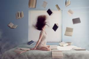 Woman on bed w books