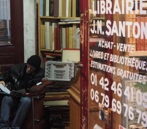 Alter Mann sitzt zwischen Büchern in einem Antiquariat in Paris