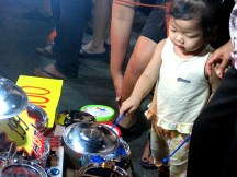 A young girl stops to fancy a child's drum set at the night market.