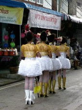Baton girls march down the road in line.