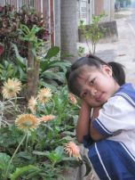 My Niece, Pissa, Waits Outside Our House Near the Flowers for the Morning School Bus to Pick Her Up