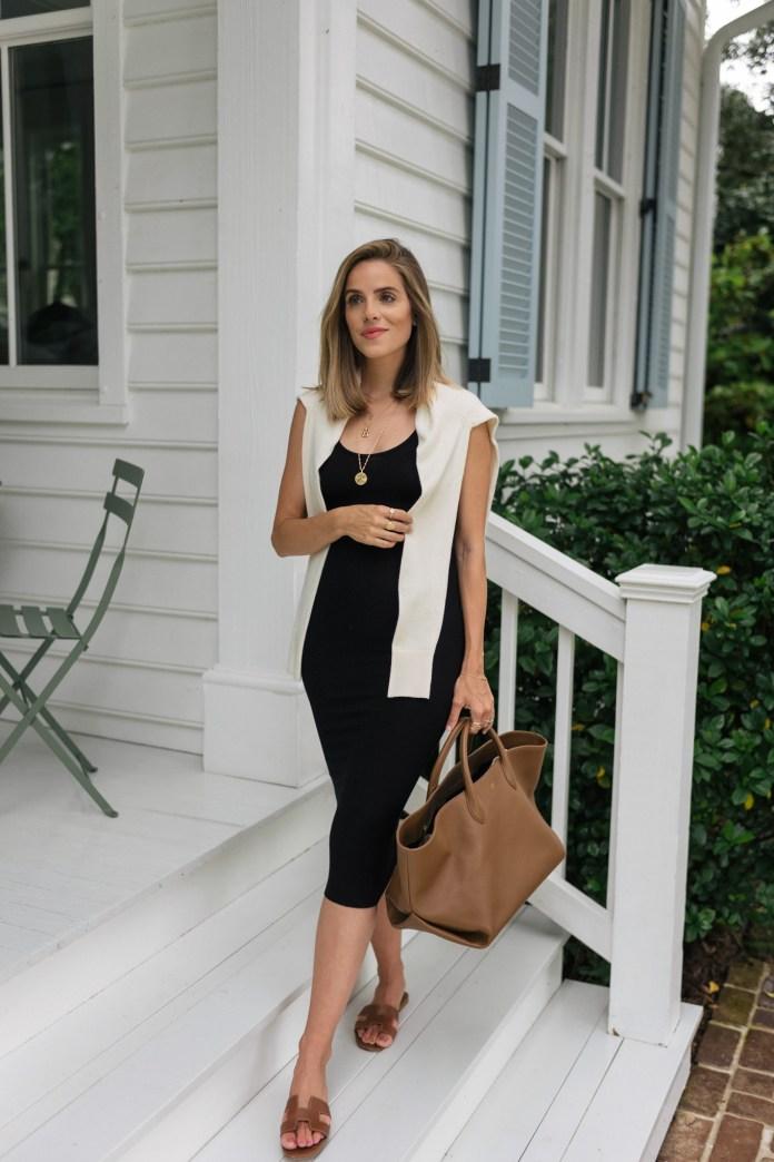 black dress beige sweater brown bag