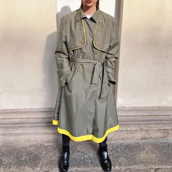 Model standing firmly in the Best Upcycled Waterproof Trench coat, made in Italy. Khaki raincoat with yellow trim.