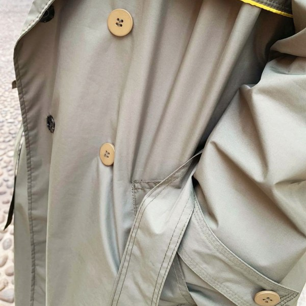 Close up image of buttons on the khaki trench coat by Julia Di Lorenzo fashion.