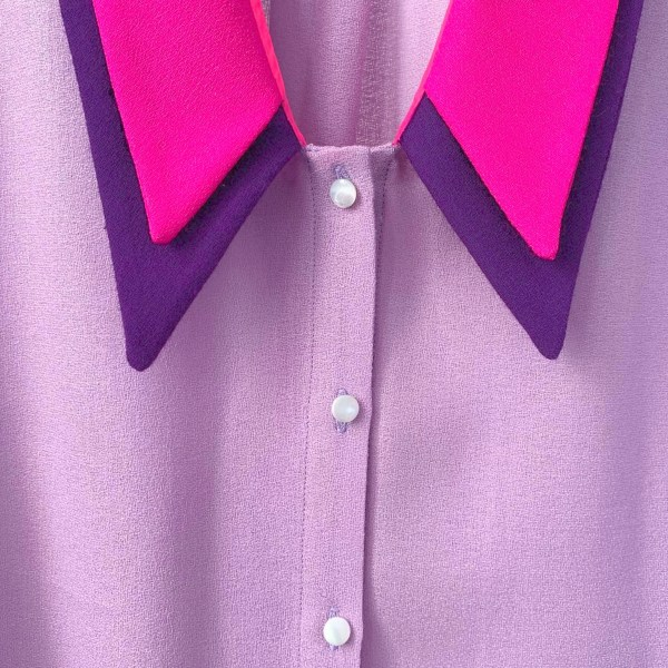 purple blouse with pink and deep purple triangular collar. White buttons on blouse. Linen fabric closeup.