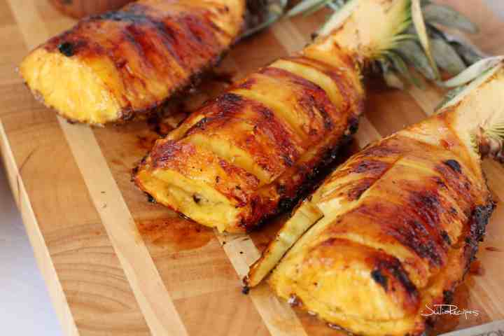 Grilled pineapple cut in wedges on wooden board