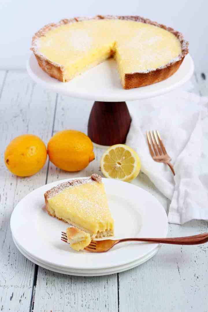Lemon tart slice on white plate with fork and lemons around