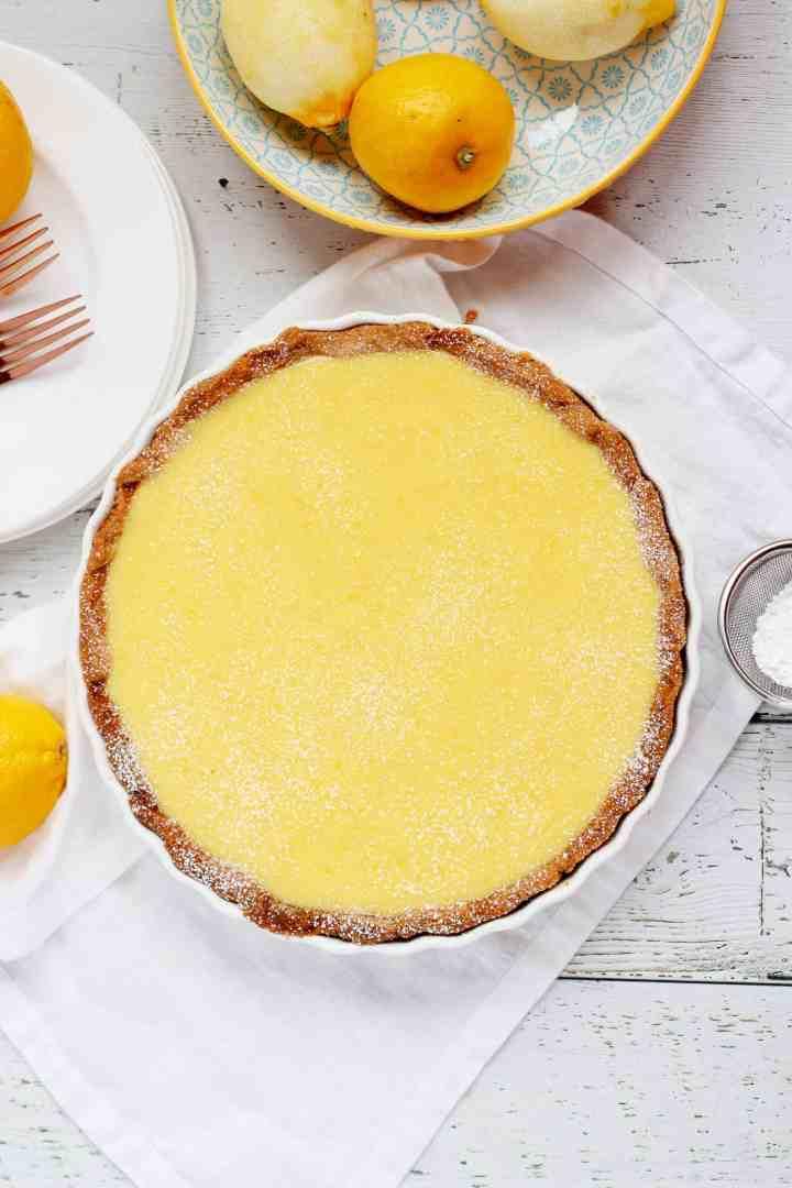 Lemon tart in pan laying on white napkin