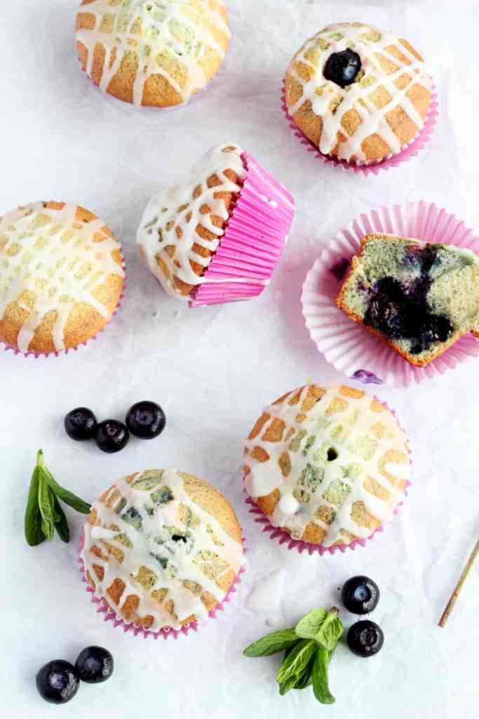 Six blueberry muffins with lemon glaze laying in parchment paper