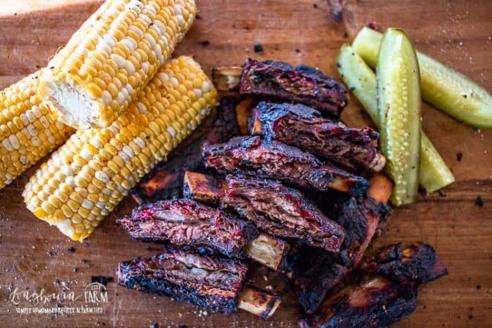 Smoked Beef Ribs with corn and pickels on wooden board