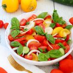 tomato and cucumber salad in white bowl