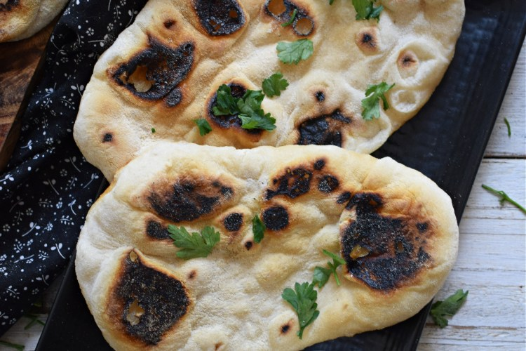 Stove top nann bread on a black plate with olive oil and parsley