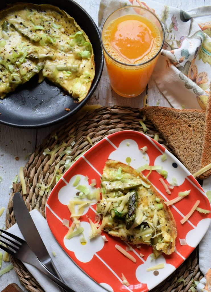 Table setting of the Spring Asparagus and Gouda Omelette with toast and a glass of juice