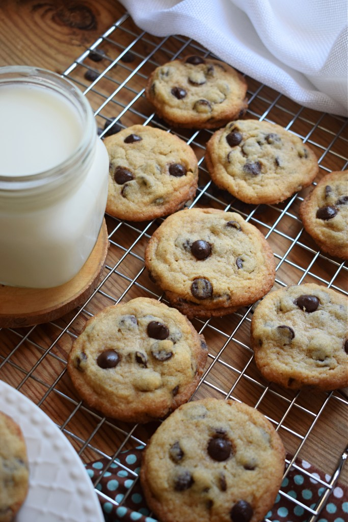 chocolate chip cookies on a cooling rack with a glass of milk