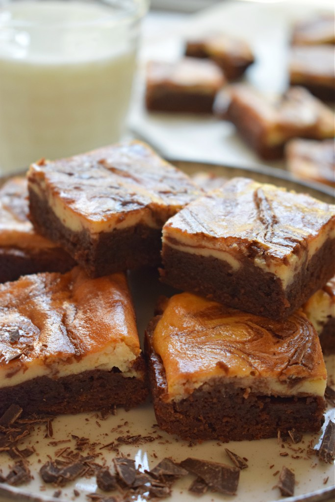 Cream Cheese Brownies stacked on a plate with a glass of milk in the background