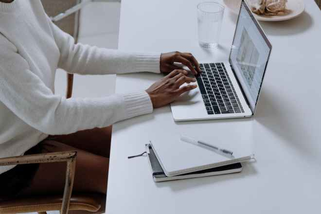 person in white long sleeve shirt using macbook pro